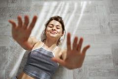 Πορτρέτο των νέων τρυφερών όμορφων χεριών τεντώματος χαμόγελου κοριτσιών στη κάμερα που βρίσκεται στο πάτωμα στο πρωί sunlights α Στοκ Εικόνα
