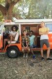 Πορτρέτο των νέων φίλων με το φορτηγό τροχόσπιτων που σταθμεύουν στη θέση για κατασκήνωση στοκ εικόνα με δικαίωμα ελεύθερης χρήσης