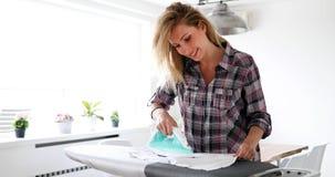 Πορτρέτο των νέων όμορφων ενδυμάτων σιδερώματος γυναικών Στοκ Φωτογραφία