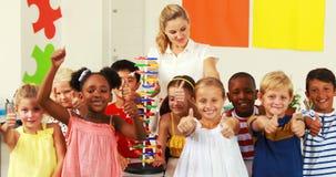Πορτρέτο των παιδιών και του δασκάλου που κάνουν τους αντίχειρες επάνω στο εργαστήριο φιλμ μικρού μήκους
