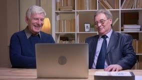 Πορτρέτο των παλαιών επιχειρηματιών που εργάζονται με το lap-top και που συζητούν χαρωπά το πρόγραμμα απόθεμα βίντεο