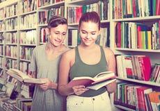 Πορτρέτο των πελατών εφήβων και κοριτσιών που εξετάζουν το ανοικτό βιβλίο στοκ φωτογραφία