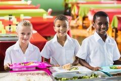 Πορτρέτο των σχολικών παιδιών που έχουν το μεσημεριανό γεύμα κατά τη διάρκεια του χρόνου σπασιμάτων Στοκ Εικόνες