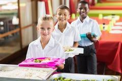 Πορτρέτο των σχολικών παιδιών που έχουν το μεσημεριανό γεύμα κατά τη διάρκεια του χρόνου σπασιμάτων Στοκ φωτογραφία με δικαίωμα ελεύθερης χρήσης
