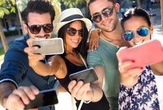 Πορτρέτο των φίλων ομάδας που παίρνουν τις φωτογραφίες με ένα smartphone Στοκ Φωτογραφίες
