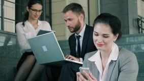 Πορτρέτο των φιλικών συναδέλφων που κάνουν επιχειρήσεις που χρησιμοποιούν υπαίθρια τις συσκευές τους φιλμ μικρού μήκους