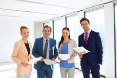 Πορτρέτο των χαμογελώντας επιχειρηματιών με τα έγγραφα στην αρχή Στοκ εικόνα με δικαίωμα ελεύθερης χρήσης