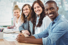 Πορτρέτο των χαμογελώντας επιχειρηματιών που κάθονται στη σειρά στο γραφείο Στοκ εικόνες με δικαίωμα ελεύθερης χρήσης