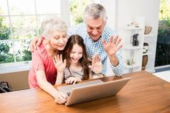 Πορτρέτο των χαμογελώντας παππούδων και γιαγιάδων και της εγγονής που χρησιμοποιούν το lap-top στοκ φωτογραφία με δικαίωμα ελεύθερης χρήσης