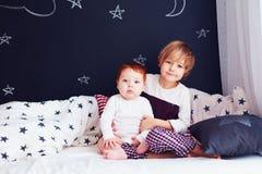 Πορτρέτο των χαριτωμένων αδελφών στο κρεβάτι το πρωί Στοκ Φωτογραφία