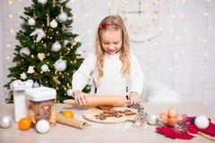 Πορτρέτο των χαριτωμένων μπισκότων Χριστουγέννων ψησίματος κοριτσιών στην κουζίνα με το Γ στοκ φωτογραφίες