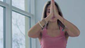 Πορτρέτο των όμορφων ανοιχτόχρωμης επιδερμίδας φέρνοντας χεριών κοριτσιών σε Namaste φιλμ μικρού μήκους