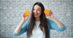 Πορτρέτο των όμορφων πορτοκαλιών και του χαμόγελου γυναικείας εκμετάλλευσης στο υπόβαθρο τουβλότοιχος απόθεμα βίντεο