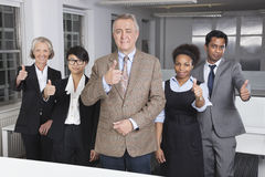 Πορτρέτο των multiethnic gesturing αντίχειρων επιχειρηματικών μονάδων επάνω στο γραφείο στοκ φωτογραφίες