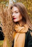 Πορτρέτο φθινοπώρου, νέο όμορφο κορίτσι με μακρυμάλλη στη φύση με το κίτρινο χαρτομάνδηλο στο λαιμό της στοκ εικόνες