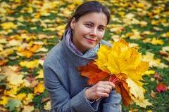 Πορτρέτο φθινοπώρου της νέας γυναίκας στα κίτρινα φύλλα υπό εξέταση στο πάρκο πτώσης Καυκάσιο κορίτσι brunette στο πάρκο φθινοπώρ Στοκ Εικόνες