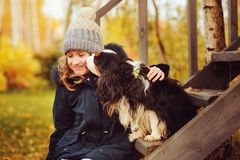 Πορτρέτο φθινοπώρου του ευτυχούς παιχνιδιού κοριτσιών παιδιών με το σκυλί σπανιέλ της στον κήπο στοκ εικόνες