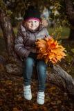 Πορτρέτο φθινοπώρου του χαριτωμένου χαμογελώντας μικρού κοριτσιού με τα φύλλα σφενδάμου στοκ εικόνες