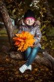 Πορτρέτο φθινοπώρου του χαριτωμένου χαμογελώντας μικρού κοριτσιού με τα φύλλα σφενδάμου στοκ φωτογραφίες