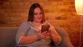 Πορτρέτο χαλαρωμένος συν τη μακρυμάλλη πρότυπη προσοχή μεγέθους στο smartphone και το γέλιο στην άνετη εγχώρια ατμόσφαιρα φιλμ μικρού μήκους