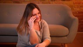 Πορτρέτο χαλαρωμένος συν τη μακρυμάλλη πρότυπη συνεδρίαση μεγέθους στο πάτωμα που έχει ένα voicecall στο smartphone στο άνετο σπί απόθεμα βίντεο