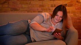 Πορτρέτο χαλαρωμένος συν το μακρυμάλλες πρότυπο μεγέθους που βρίσκεται στον καναπέ που κουβεντιάζει ευτυχώς στο smartphone στην ά απόθεμα βίντεο