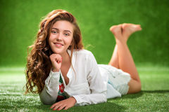 Πορτρέτο χαμογελώντας της αρκετά νέας γυναίκας, που βάζει στη χλόη Στοκ Εικόνες