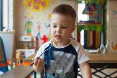 Πορτρέτο χαριτωμένου λίγος καυκάσιος χρονών χυμός φρούτων κατανάλωσης παιδιών αγοριών μικρών παιδιών 3 σε ένα γυαλί, συνεδρίαση α στοκ εικόνα