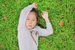 Πορτρέτο χαριτωμένο λίγου ασιατικού κοριτσιού παιδιών που βρίσκεται στον πράσινο χορτοτάπητα με το αστείο πρόσωπο στοκ εικόνες με δικαίωμα ελεύθερης χρήσης