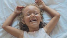 Πορτρέτο χαριτωμένο να βρεθεί κοριτσιών παιδιών στο κρεβάτι, της εξέτασης τη κάμερα και του γέλιου απόθεμα βίντεο