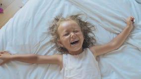 Πορτρέτο χαριτωμένο να βρεθεί κοριτσιών παιδιών στο κρεβάτι, της εξέτασης τη κάμερα και του γέλιου φιλμ μικρού μήκους