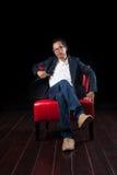 Πορτρέτο χρονών της ασιατικής συνεδρίασης ατόμων 45 στον κόκκινο καναπέ ενάντια στο β στοκ φωτογραφία με δικαίωμα ελεύθερης χρήσης