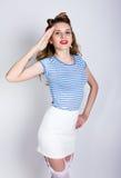 Πορτρέτο όμορφου ενός ξανθού σε ένα ριγωτό πουκάμισο, μια άσπρη φούστα και δαντελλωτός γυναικείες κάλτσες, χαιρετισμός ναυτικών μ Στοκ Εικόνες