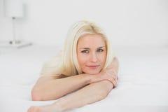 Πορτρέτο όμορφο ξανθό να βρεθεί χαμόγελου στο κρεβάτι Στοκ εικόνες με δικαίωμα ελεύθερης χρήσης