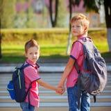 Πορτρέτο δύο λατρευτά αγόρια με το σακίδιο πλάτης κοντά στο για τους πεζούς crossin Στοκ Φωτογραφία