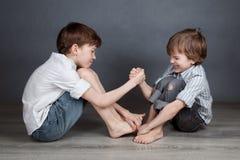 Πορτρέτο δύο ευτυχών αδελφών στο agray υπόβαθρο στοκ εικόνα