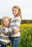 Πορτρέτο δύο που αγκαλιάζουν τα χαριτωμένα μικρά κορίτσια στοκ εικόνα