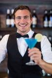 Πορτρέτο bartender που εξυπηρετεί μπλε martini Στοκ Εικόνα