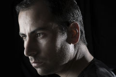 Πορτρέτο Headshot του νεαρού άνδρα στο μαύρο σκληρό φως υποβάθρου Στοκ Εικόνα