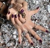 Πορφυρά καρφιά και ασήμι στιλβωτικής ουσίας σχεδίων που συσσωρεύουν τα δαχτυλίδια και bracel Στοκ εικόνες με δικαίωμα ελεύθερης χρήσης