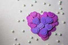 Πορφυρά καρδιές και μαργαριτάρια που βρίσκονται σε ένα μπεζ ύφασμα Στοκ Φωτογραφία