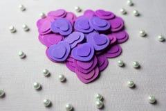 Πορφυρά καρδιές και μαργαριτάρια που βρίσκονται σε ένα μπεζ ύφασμα Στοκ Εικόνες