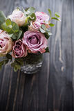 Πορφυρά, μωβ φρέσκα θερινά τριαντάφυλλα χρώματος στο βάζο με τη μαύρη ταμπλέτα Στοκ Φωτογραφία