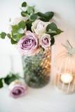Πορφυρά, μωβ φρέσκα θερινά τριαντάφυλλα χρώματος στο βάζο με τον άσπρο τοίχο β Στοκ Εικόνες