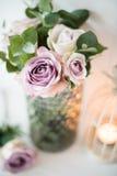 Πορφυρά, μωβ φρέσκα θερινά τριαντάφυλλα χρώματος στο βάζο με τον άσπρο τοίχο β Στοκ Φωτογραφία