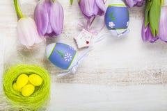 Πορφυρά τουλίπες ανθοδεσμών και αυγά Πάσχας σε έναν ελαφρύ ξύλινο πίνακα Στοκ εικόνα με δικαίωμα ελεύθερης χρήσης