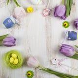 Πορφυρά τουλίπες ανθοδεσμών και αυγά Πάσχας σε έναν ελαφρύ ξύλινο πίνακα Στοκ φωτογραφίες με δικαίωμα ελεύθερης χρήσης