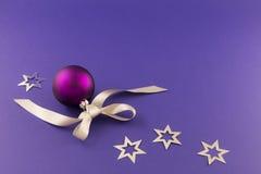 Πορφυρή σφαίρα Χριστουγέννων με τα αστέρια και την γκρίζα κορδέλλα Στοκ Εικόνες