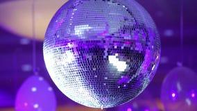 Πορφυρή σφαίρα disco που απεικονίζει τις ακτίνες στο υπόβαθρο των μπαλονιών κλείστε επάνω φιλμ μικρού μήκους