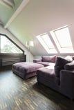 Πορφυρός καναπές στο αττικό δωμάτιο σαλονιών Στοκ φωτογραφίες με δικαίωμα ελεύθερης χρήσης